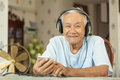 Happy Asian Senior Man Headphones Listening Music Stock Images - 84202074