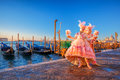 Carnival Masks Against Gondolas In Venice, Italy Stock Images - 84208384