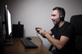 Young Gamer In Headphones And Glasses Using Console And Computer For Playing Game Royalty Free Stock Images - 84225179