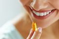 Close Up Of Beautiful Woman Taking Fish Oil Capsule In Mouth Royalty Free Stock Image - 84239576