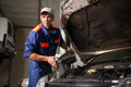 Portait Of Mechanic Fixing Car Engine In Repair Shop Royalty Free Stock Photo - 84416145