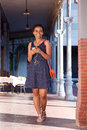 Smiling Young Black Woman Walking With Cellphone And Earphones Stock Photography - 84680742
