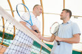 Men Shaking Hands Over Tennis Court Net Royalty Free Stock Photography - 84765187