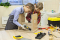 Boys With Screwdrivers And Drill Repairing Wooden Stool Royalty Free Stock Photo - 84783085