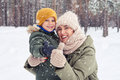 Smiling Mom Hugging Her Son Under The Snowfall In The Forest Royalty Free Stock Photo - 84868435