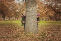 Group Of Young People Hidden Behind A Tree. Autumn Landscape Royalty Free Stock Photo - 84934435
