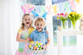 Kids With Eggs Basket On Easter Egg Hunt Stock Photos - 84951763