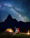 Romantic Couple Hikers Looking At The Shines Starry Sky At Night. Happy Pair Sitting Near Camp And Campfire Stock Images - 85035074