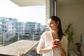 Woman Relaxing On Balcony Holding Cup Of Coffee Or Tea Stock Photography - 85068582