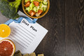 Food And Sheet Of Paper With A Diet Plan On A Dark Wooden Table. Royalty Free Stock Image - 85073716