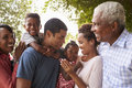 Multi Generation Black Family Look At Each Other In Garden Stock Photos - 85190553