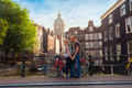 Two Lovers Person In Amsterdam On A Background Of Multi-colored House In The Dutch Style Stand And Hold Hands. Stock Images - 85250394