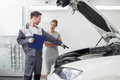 Young Male Repairman Explaining Car Engine To Female Customer In Automobile Repair Shop Royalty Free Stock Image - 85283896