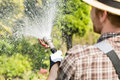 Rear View Of Gardener Watering Plants At Garden Royalty Free Stock Images - 85295689