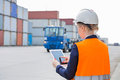 Rear View Of Female Engineer Using Tablet PC In Shipping Yard Stock Photos - 85318753