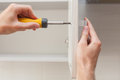 The Worker Sets A New Handle On The White Cabinet With A Screwdriver. Royalty Free Stock Photography - 85348647