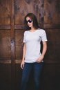 Woman Wearing White T-shirt In Front Of Wooden Wall Stock Photo - 85376470