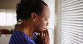 An Older Black Woman Mournfully Looks Out Her Window Stock Image - 85382481