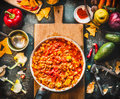 Vegetarian Chili Con Carne Dish In Pan On Wooden Cutting Board With Spices And Vegetables Cooking Ingredients On Dark Kitchen Tabl Royalty Free Stock Photo - 85483275