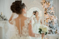 Beautiful Bride In A Wedding Dress At A Mirror In Christmas. Gir Royalty Free Stock Photos - 85614888