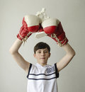 Boy With His Hands Raised In Boxing Gloves In A Victory Gesture With A Figurine Of A Boxer Royalty Free Stock Photos - 85615758