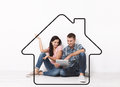 Happy Young Couple Sitting On Floor Using A Tablet For Shopping And Entertainment. Layout. Drawing House As A Background Royalty Free Stock Images - 85634249