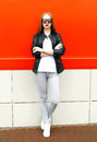 Fashion Stylish Woman Wearing A Rock Black Jacket And Sunglasses In City Over Red Stock Photo - 85668290