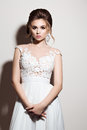 Front View Of Brunette Bride In Wedding Dress With Elements Of Lace And Big Earrings Posing In Studio. Beautiful Woman In Luxury D Stock Photo - 85928190