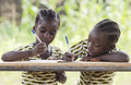 Two Young African Girls Writing Outdoors Stock Images - 85990074