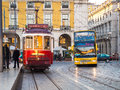 Transport In Lisbon: Typical Old Tram And A Touristic Bus On The Royalty Free Stock Photography - 86172907