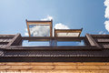 Open Skylights Mansard Windows In Wooden House With Tile Against Blue Sky. Royalty Free Stock Photo - 86242125