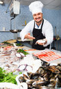Seller In White Cap And Black Apron Showing Counter With Fish Royalty Free Stock Photo - 86307425
