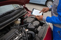 Mechanic With Digital Tablet While Examining Car Royalty Free Stock Photo - 86373165