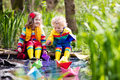 Kids Playing With Colorful Paper Boats In A Park Royalty Free Stock Images - 86394139