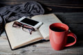 Grey Cozy Knitted Scarf With Cup Of Coffee Or Tea, Phone, Glasses And Open Book On A Wooden Table. Stock Images - 86407894