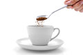 Hand Pours Instant Coffee From A Spoon In A Coffee Cup Royalty Free Stock Images - 86570559