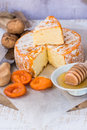 Soft Cheese With Cut Off Slice Creamy Texture, Orange Rind With Mold, French, German, Alps, Honey Dipper, Walnuts, Dried Apricots, Royalty Free Stock Photography - 86574697