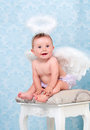 Small And Happy Angel Smiling And Sitting On A Chair. Royalty Free Stock Photos - 86702278