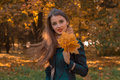 Young Girl Stands In The Park And Holds Autumn Leaves In Hand Stock Photos - 86784993