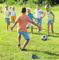 Group Of Smiling Kids Playing Football Together On Green Lawn In Royalty Free Stock Photography - 86789457