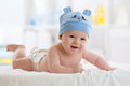 Funny Baby Boy Lying On Stomach On Bed In Living Room Stock Image - 86792061