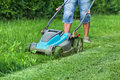 Man Cutting The Grass With A Lawn Mower Stock Image - 86890791