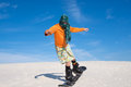 Man Wearing A Scarf Engaged In Snowboarding In Desert Royalty Free Stock Images - 86919099