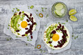 Mexican Huevos Rancheros Tacos. Breakfast Tostadas With Black Beans, Avocado, Fried Egg, Microgreens, Sriracha Ketchup. Top View Stock Photo - 86996100