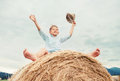 Happy Boy Sits Over Big Rolling Haystack Royalty Free Stock Images - 87307449