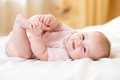 Happy Baby Girl Lying On White Sheet And Holding Her Legs Stock Images - 87332824