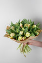 Woman Hand Holding Soft Yellow Tulips Flowers On White Background. Bouquet Decorated With Kraft Paper Royalty Free Stock Photos - 87351278