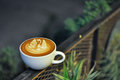 Coffee Cup With Latte Art On The Metal Fence At Night Royalty Free Stock Image - 87447996