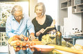 Senior Couple Cooking Healthy Food And Drinking Red Wine Stock Image - 87450811