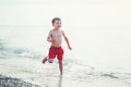 White Caucasian One Young Little Boy In Red Swim Shorts Running On Beach By Water Stock Images - 87456754